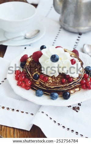 Breakfast with homemade thin pancakes with whipped cream and fresh berries - raspberry, black and red currant and bilberry