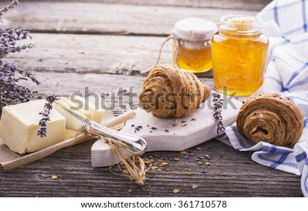 Breakfast with honey butter fresh croissants in the early morning on a simple wooden table in rustic style with blue textiles. The concept is simple natural homemade food. selective Focus - stock photo