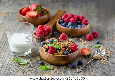 Breakfast with muesli and berries in wooden bowls  - stock photo