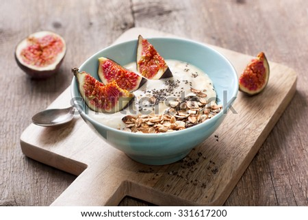 Breakfast with muesli, yogurt, figs and chia seeds in a blue bowl on a wooden background - stock photo