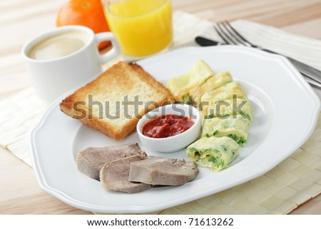 Breakfast with omelet, veal tongue, toasts, tomato sauce, coffee, and orange juice