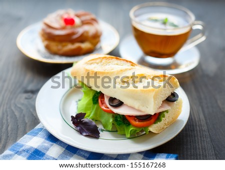Breakfast with sandwich, tea and cake - stock photo