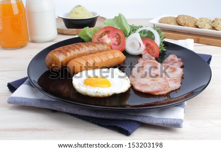 Breakfast with sausage, bacon, fried egg, orange juice, milk and cookies isolated on  white background. - stock photo