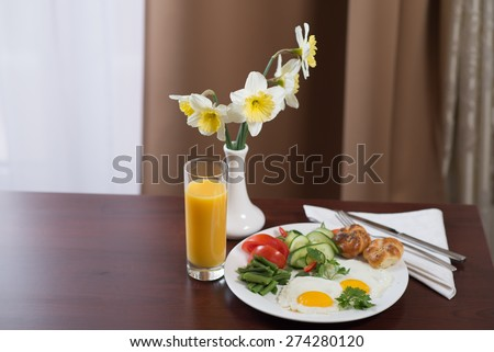 Breakfast with scrambled eggs and orange juice in a hotel room - stock photo