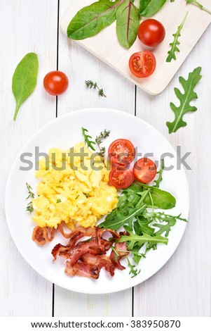 Breakfast with scrambled eggs, bacon and vegetable salad, top view - stock photo