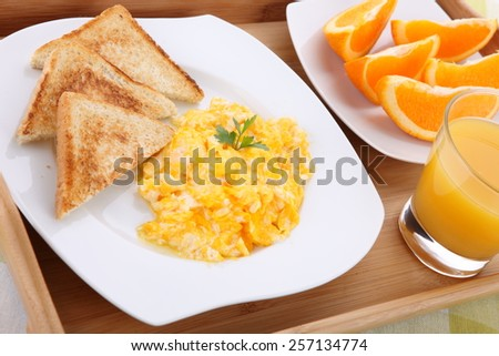 breakfast with scrambled eggs, toasts, juice  - stock photo