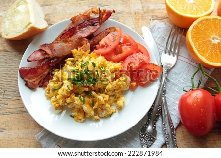 Breakfast with scrambled eggs with bacon and fresh tomatoes - stock photo