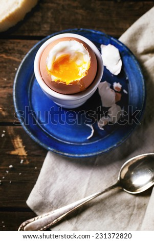 Breakfast with soft-boiled egg, served with bread over old wooden table. Top view. - stock photo