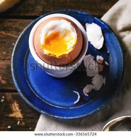 Breakfast with soft-boiled egg, served with bread over old wooden table. Top view. Square image with selective focus - stock photo