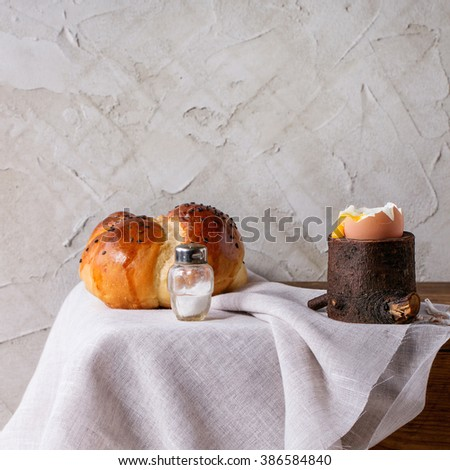 Breakfast with started eating soft-boiled egg with pouring yolk in wooden eggcup and bread served with salt on white cloth over white table. With plastered wall at background. Square image - stock photo