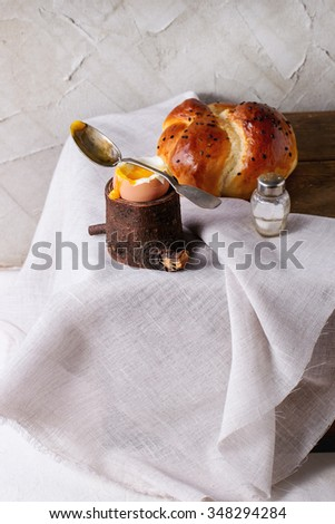 Breakfast with started eating soft-boiled egg with pouring yolk in wooden eggcup and home made bread served on wooden chest with white cloth over white table. With plastered wall at background - stock photo