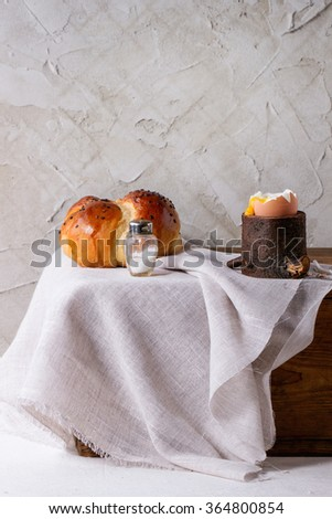 Breakfast with started eating soft-boiled egg with pouring yolk in wooden eggcup and home made bread served with salt on wooden chest with white cloth over table. With plastered wall at background - stock photo