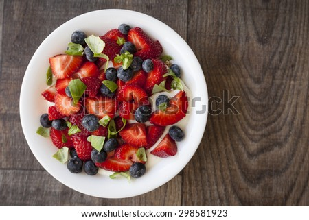 Breakfast with strawberry, blueberry, basil leaves and yogurt.