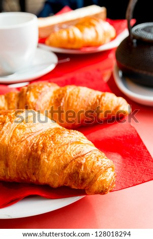 Breakfast with tea and croissants in a basket on table
