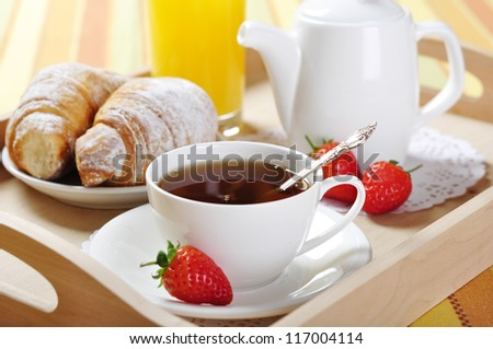 Breakfast with tea and croissants in a wooden tray on table - stock photo
