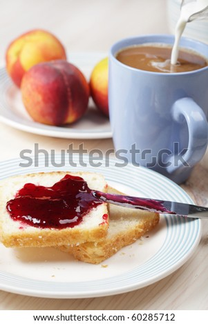 Breakfast with toasts, black currant jelly, peaches and coffee