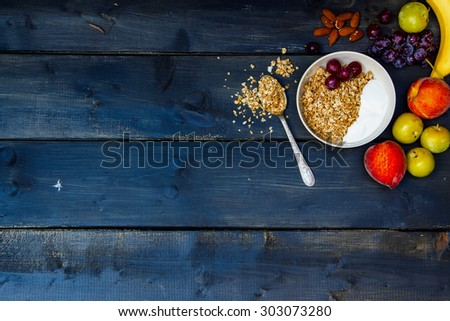 Breakfast with yogurt, fresh fruits, almonds and homemade granola on old wooden background with space for text. Health and diet concept. - stock photo