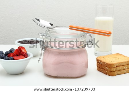 breakfast with yogurt in glass jar fruit toast and milk on white table