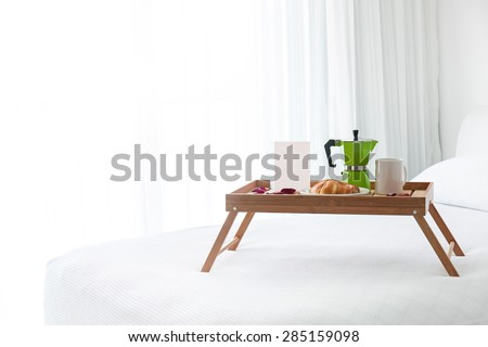 Breakfast wooden tray with coffee percolator, white blank card and croissant on bed. Light from window inside the room - stock photo
