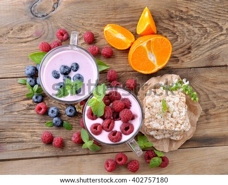 Breakfast. Yogurt with berries blueberries and raspberries, slices and ripe orange.Healthy eating. - stock photo