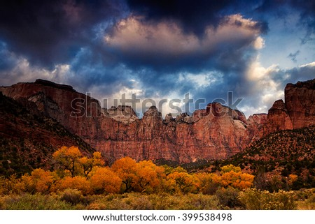 Breaking clouds capture morning light over the Towers of the Virgin in Utah's Zion National Park. Cottonwoods in autumn showcase their brilliant golden color.