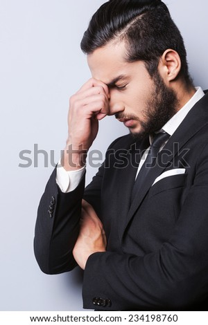 Breaking from the stress. Frustrated young man in formalwear touching head with fingers and keeping eyes closed while standing against grey background - stock photo