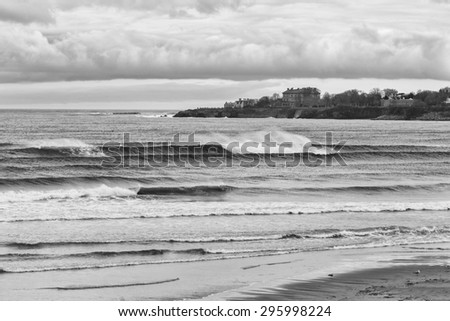 Breaking waves at Eastons beach. Newport mansions in the background. - stock photo