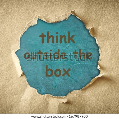 Breakthrough paper hole and the phrase think outside the box written on blue board - stock photo