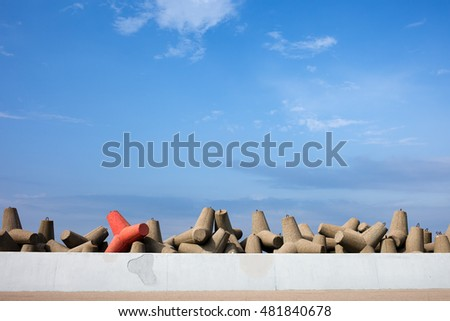Breakwater protection, solid concrete blocks with one different than others, sea wall embankment