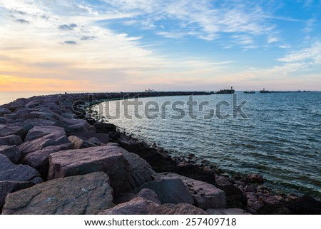 Breakwater with gates and fishing boat leaving harbor at dramatic cloudy sunset - stock photo