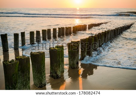 Breakwaters in waves on  the beach at the north sea in Domburg Holland in the evening sun   - stock photo