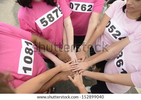 breast cancer awareness race: women in pink  joining hands for support  - stock photo