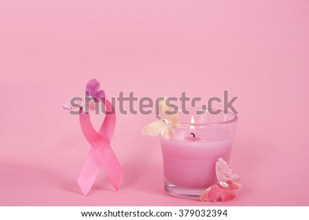 Breast Cancer Awareness ribbon loop with paper butterflies holding it up in the air, pink candle in glass burning and more paper butterflies flying up towards the ribbon - stock photo