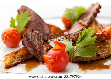 Breast of Duck with Roasted Potato Slice and Cherry Tomatoes - stock photo