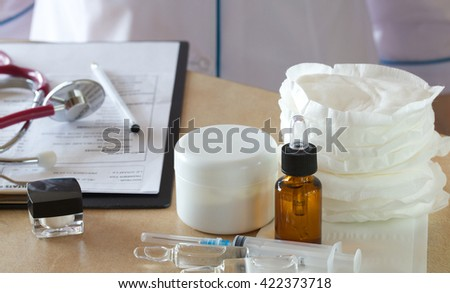 Breast pads,injections,creams,droppers bottles with essential oils on a table of a doctor - stock photo