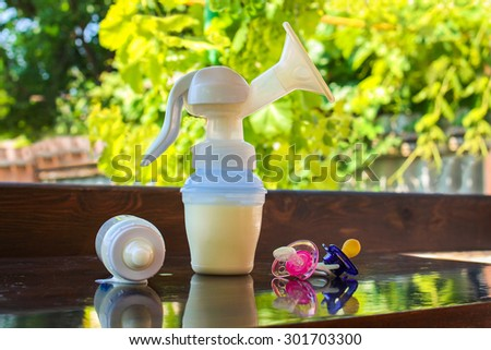 Breast pump, bottle of milk and pacifiers on the table  - stock photo