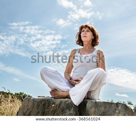 breathing outdoors - beautiful middle aged woman sitting on a stone in yoga lotus position, wearing white, seeking for balance over summer blue sky,low angle view - stock photo