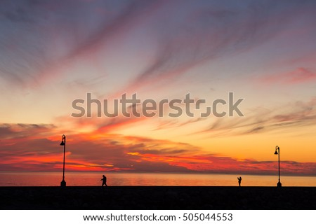 Breathtaking Sunset in Sainte-Flavie, Quebec, Canada, with silhouettes of people walking on the jetty