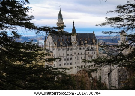 Breathtaking view behind the tree branches on fairytale Neuschwanstein Castle located high on a hill on a gray and moody winter day, Munich, Bavaria, Germany
