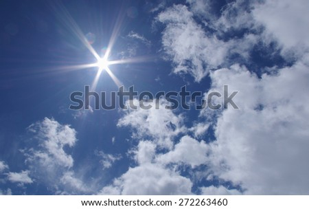 Breathtaking view of a blue sky with bright sun and clouds. - stock photo