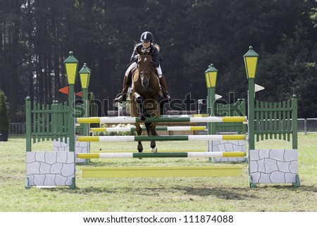 BREDA, HOLLAND - SEPT 2: Unidentified jockey on horse jumping during yearly cross country contest at Outdoor Brabant, formerly Breda Hippique on September 2, 2012 in Breda, the Netherlands - stock photo