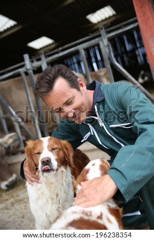 Breeder petting dogs outside the barn - stock photo