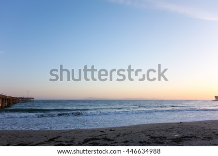 Breezy evening surf at Ventura city beach near historic wooden pear with a distant chain of Channel Islands, California
