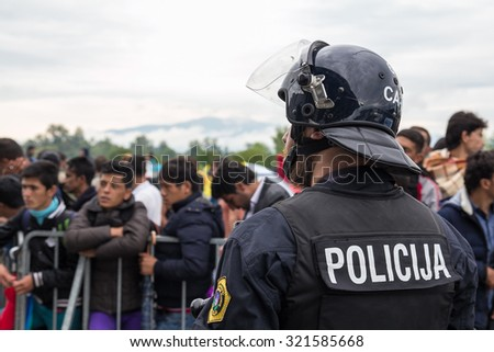 BREGANA, SLOVENIA: SEPTEMBER 19, 2015: Close up of policeman in front of group of immigrants and refugees from Middle East and North Africa at Bregana, state border between Slovenia and Croatia. - stock photo