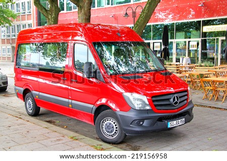 BREMEN, GERMANY - AUGUST 10, 2014: Red passenger van Mercedes-Benz Sprinter at the city street. - stock photo