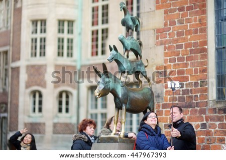 BREMEN, GERMANY - MARCH 23, 2016: Tourists taking pictures of themselves by famous statue in the center of Bremen known as The Bremen Town Musicians