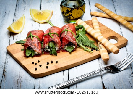 bresaola rolls with ricotta cheese and arugula - stock photo