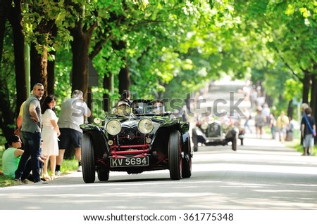 BRESCIA (BS), ITALY - MAY 14: A black and red Riley prototype, followed by OOF classic cars, takes part to the 1000 Miglia classic car race on May 14, 2015 in Brescia (BS). The cars was built in 1933. - stock photo