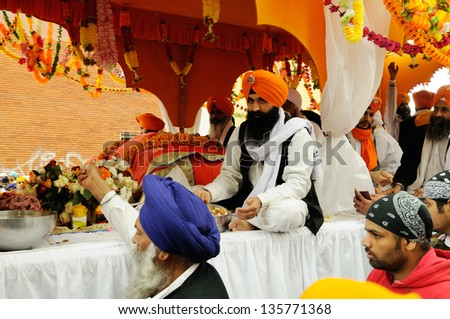 BRESCIA ITALY - APRIL 20: Sikh devotees share food, as per tradition, at the Baisakhi (harvest) Sikh festival, on April 20, 2013 in Brescia - stock photo