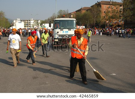 BRESCIA, ITALY - APRIL 30: Street cleaners sweep street before 'Baisakhi' procession April 30, 2005 in Brescia, Italy.  20,000 Sikh Indians residing in Italy celebrate the annual procession.